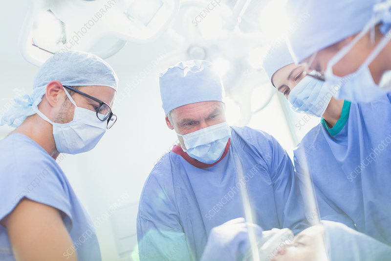 Surgeons and anaesthesiologist preparing patient