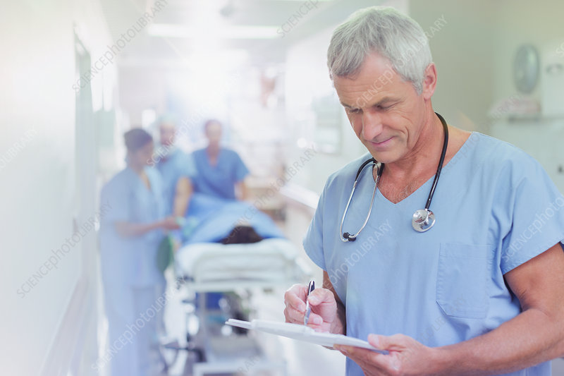 Surgeon reviewing medical record clipboard