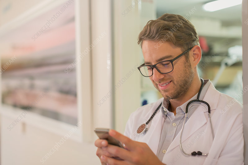 Male doctor texting with cell phone in hospital