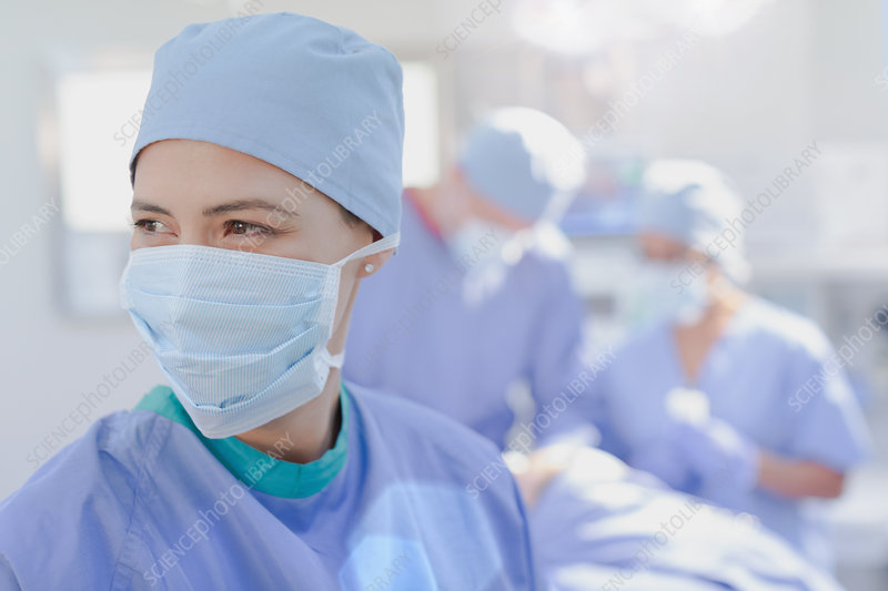 Smiling female surgeon wearing surgical mask