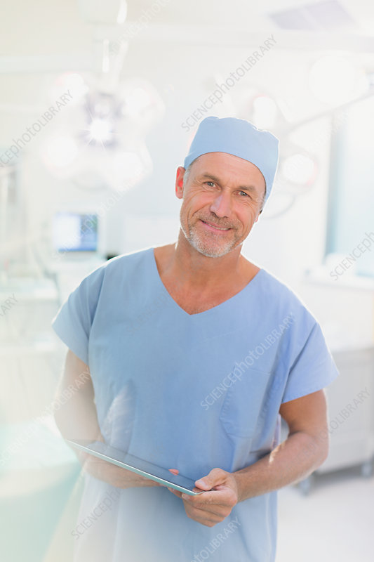 Portrait male surgeon using digital tablet