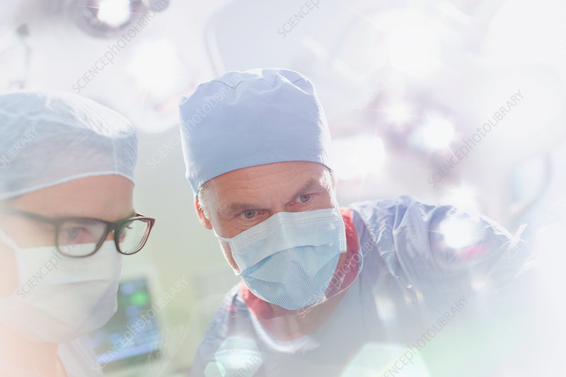 Surgeons wearing surgical mask looking down