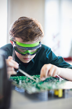 Student in goggles soldering circuit board