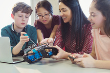 Female teacher and students programming robotics