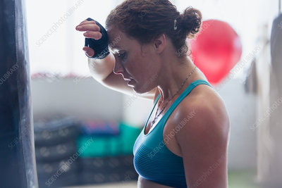 Tired female boxer wiping sweat from brow in gym