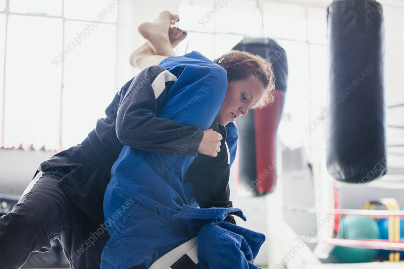 Determined woman practicing jiu-jitsu, tackling in gym