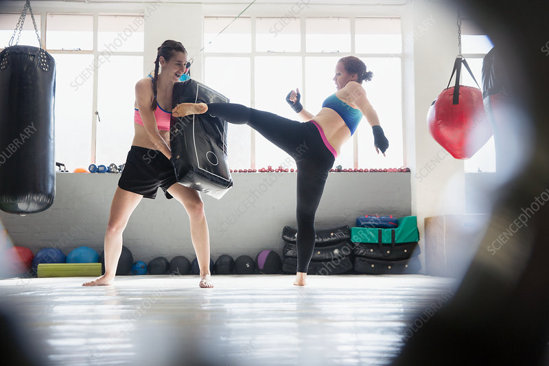 Women kickboxing with pad in gym
