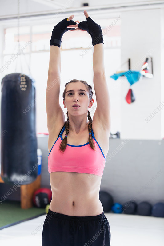 Young woman stretching with arms overhead in gym