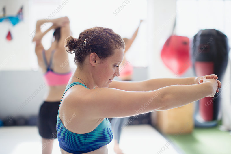Focused female boxer stretching arms in gym