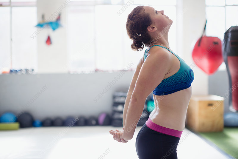 Woman stretching chest in gym