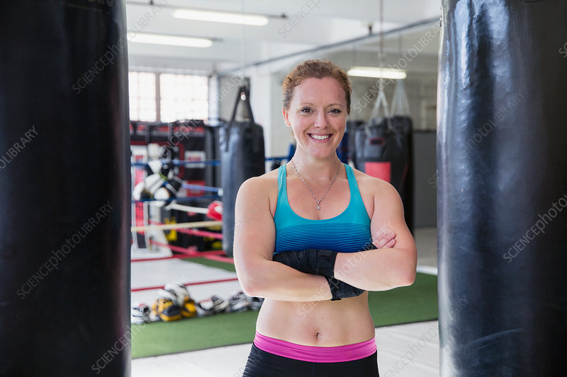 Portrait female boxer standing at punching bags