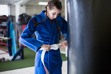 Young woman tightening jiu-jitsu belt at punching bag