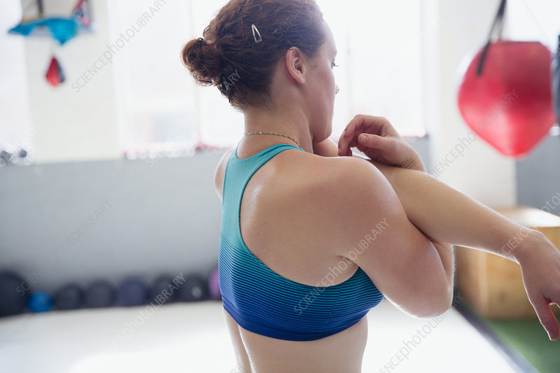 Woman stretching arm and shoulder in gym