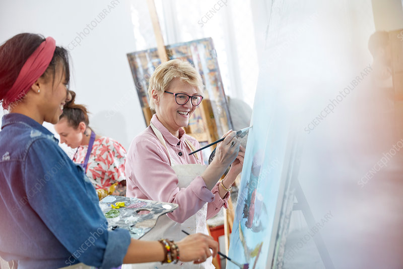 Female artists painting in art class studio