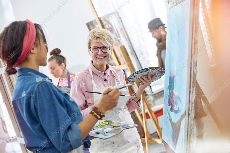 Smiling artists with paintbrushes and palettes