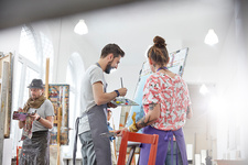 Artists painting at easel in art studio