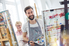 Portrait artists painting at easels