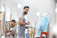 Portrait male artist painting with palette