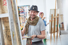 Portrait male artist painting at easel