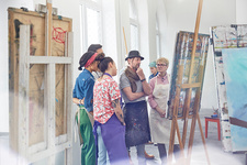 Art students and instructor critiquing painting