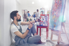 Male painter painting, examining painting