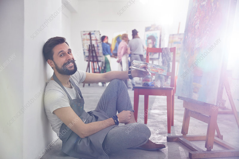 Portrait artist with palette painting at easel