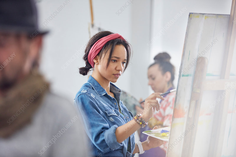 Focused female artist painting at easel