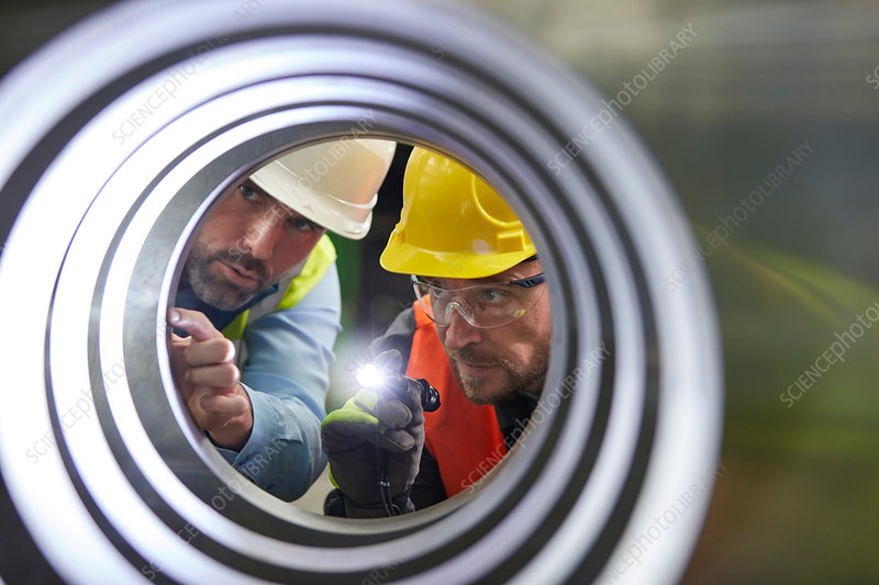 Serious engineers examining steel pipe