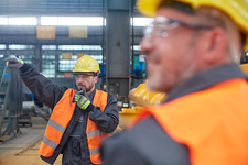 Male foreman using walkie-talkie in factory