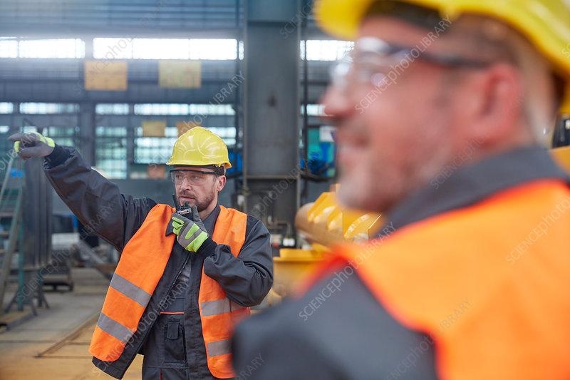 Male foreman using walkie-talkie in factory