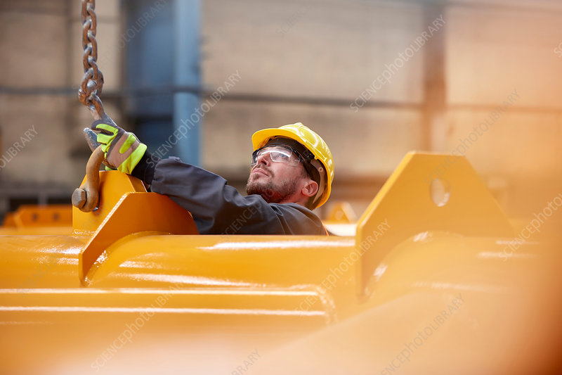 Male worker attaching chain to equipment