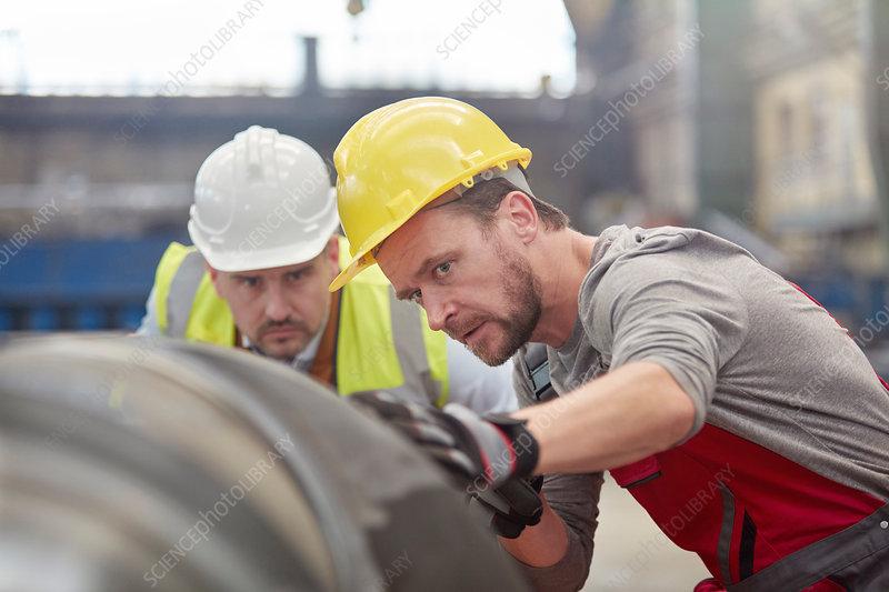 Focused engineers examining steel part