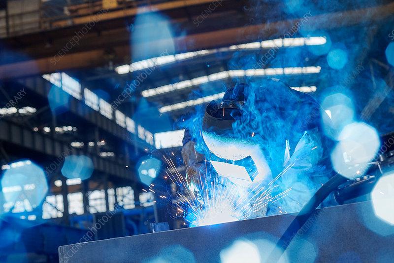 Welder in welding mask welding steel in factory