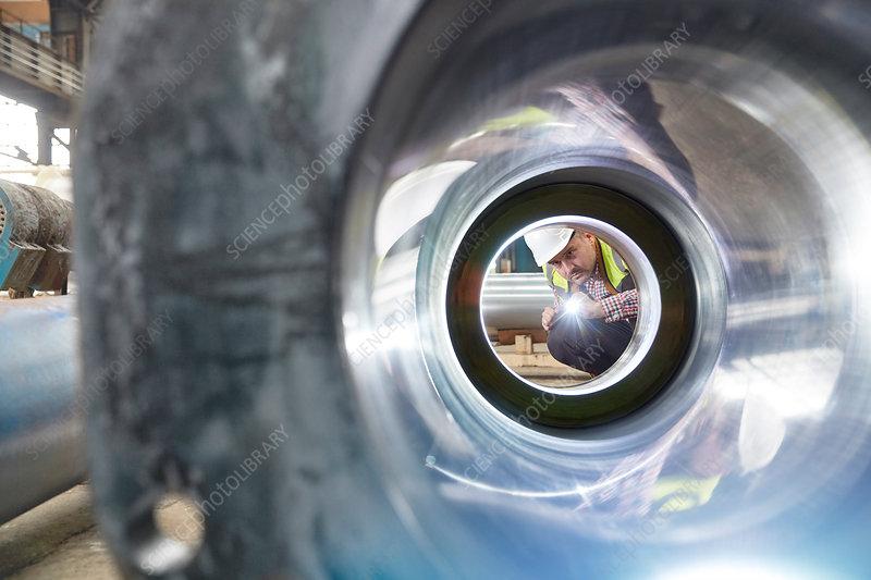 Male engineer examining steel pipe
