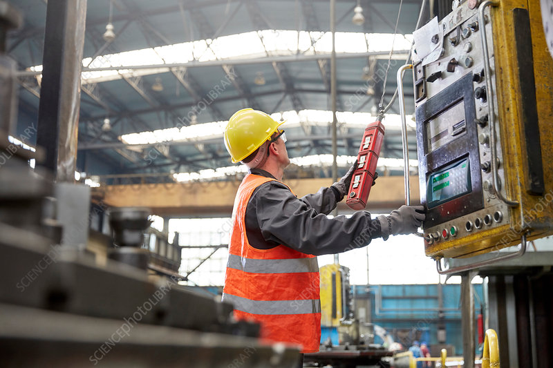 Male worker operating machinery at control panel