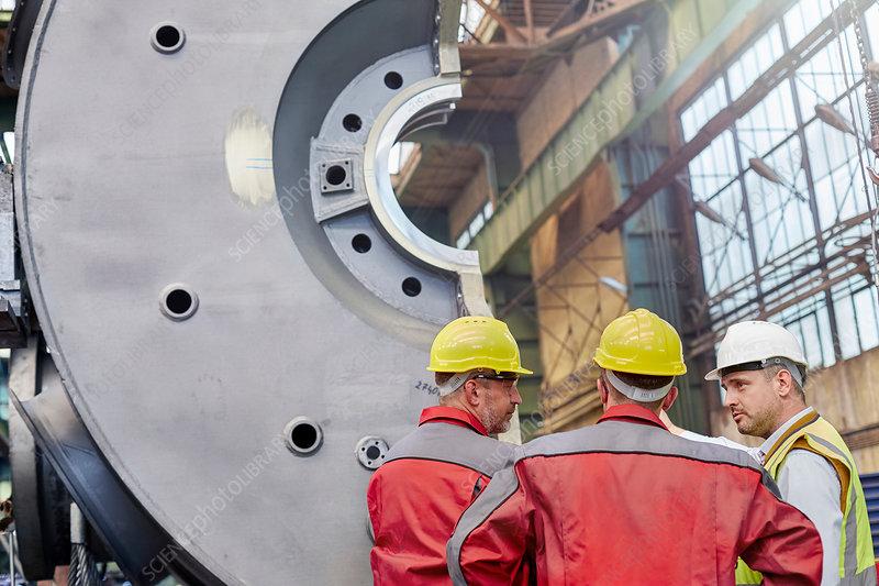 Male workers talking in steel factory