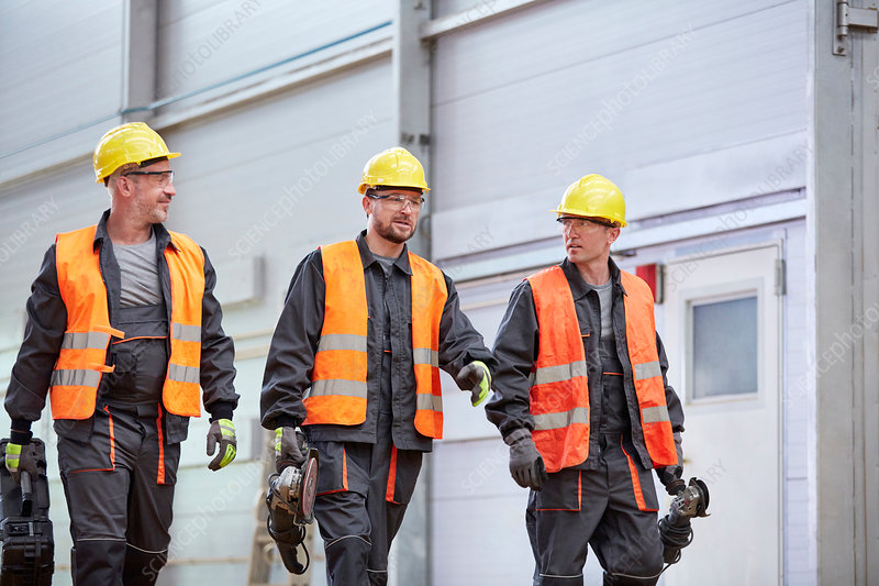 Male workers in protective clothing walking