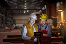 Male foreman and engineer using tablet