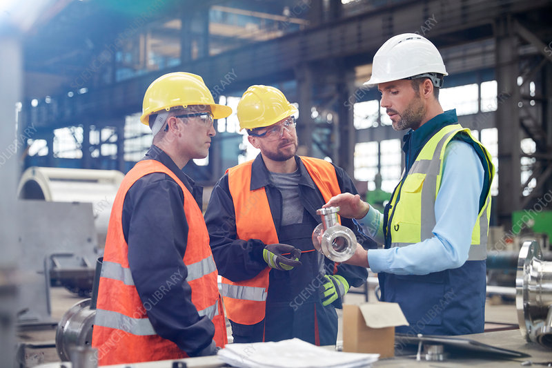 Male engineers discussing steel part in factory