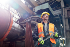 Confident male worker holding wrench in factory