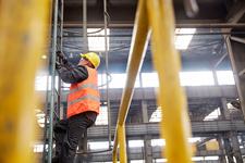 Male worker climbing ladder in factory