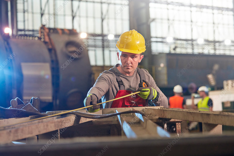 Male worker with tape measure measuring steel