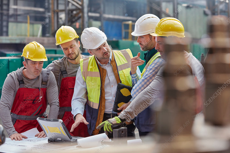Male foreman, engineers and workers at laptop