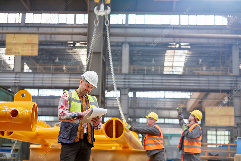 Male foreman standing near workers