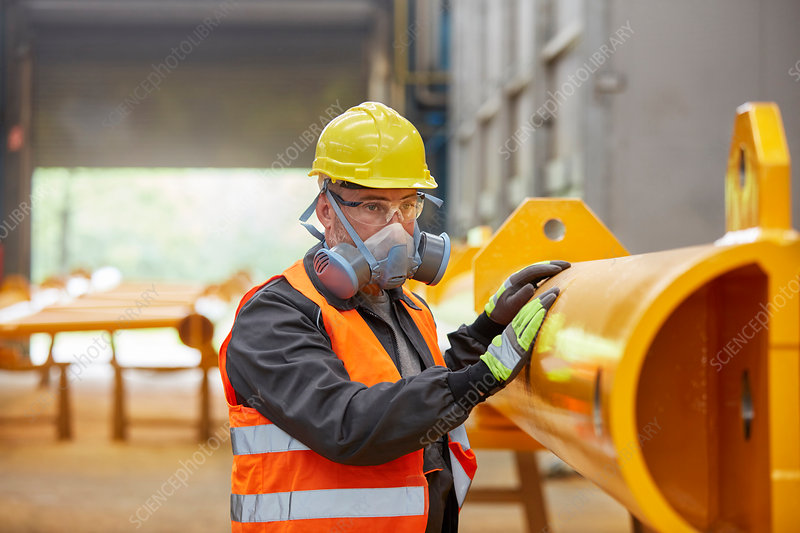 Male worker wearing protective mask in factory