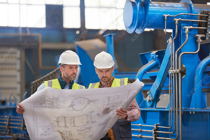 Engineers reviewing blueprints in factory