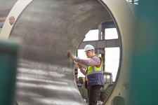 Male engineer examining large steel cylinder