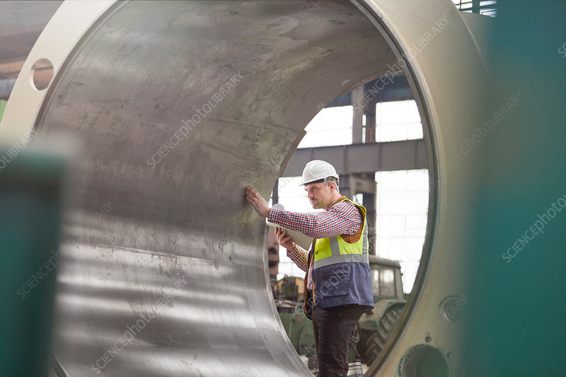 Male engineer examining large steel cylinder