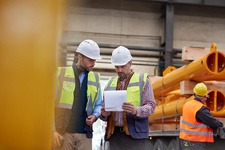 Male foreman and worker reviewing paperwork