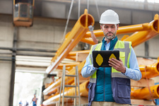 Serious male engineer using tablet in factory